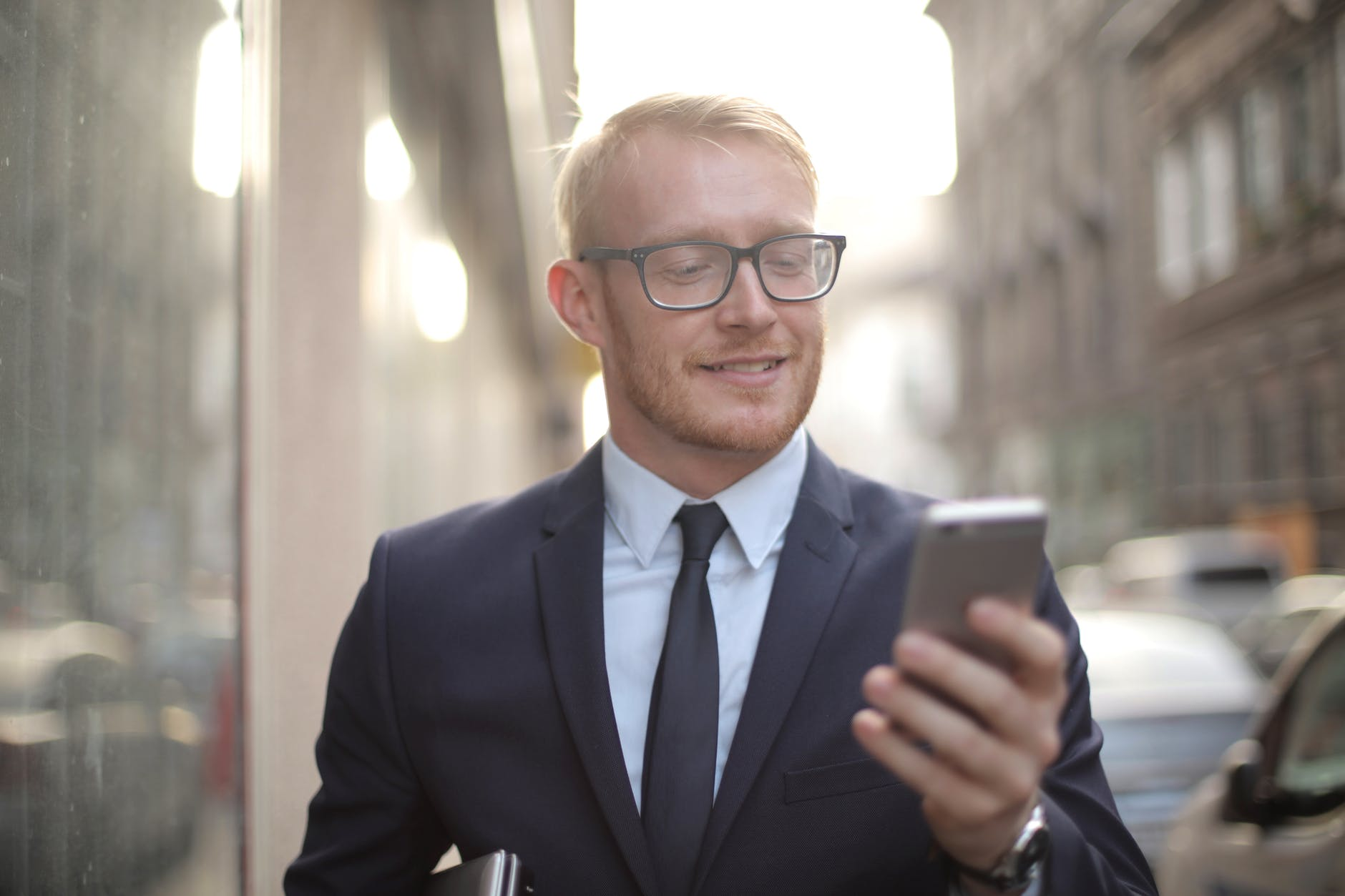 smiling male entrepreneur in eyeglasses browsing smartphone in downtown