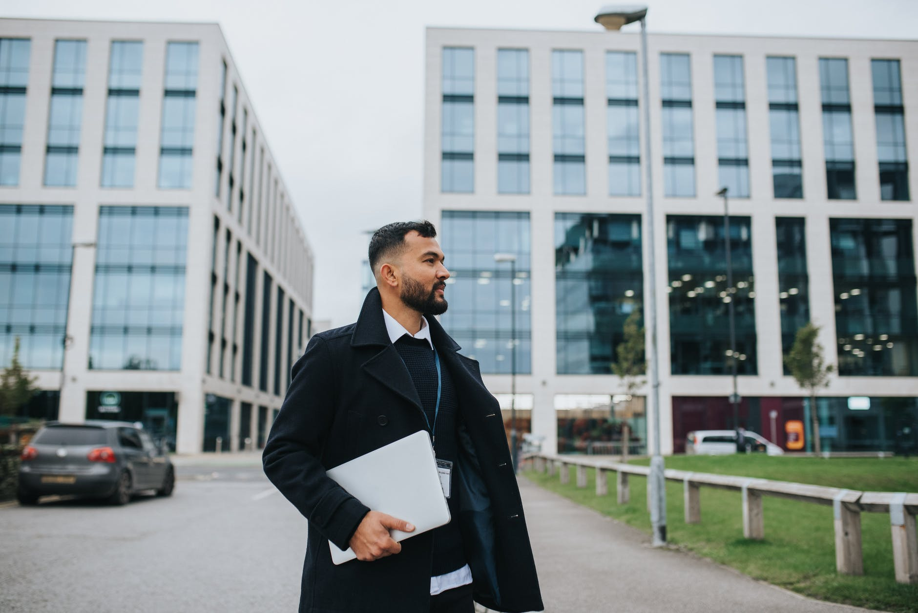trendy ethnic office employee with laptop on urban road